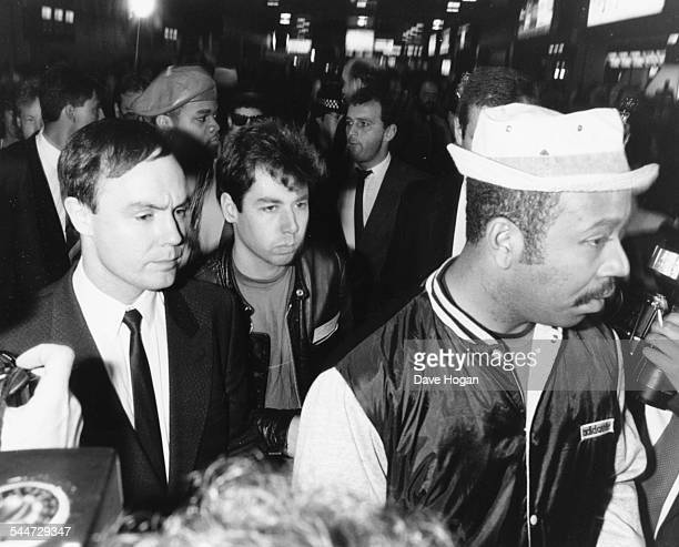 Adam Yauch member of the band 'Beastie Boys' surrounded by managers and minders as he arrives in London May 22nd 1987