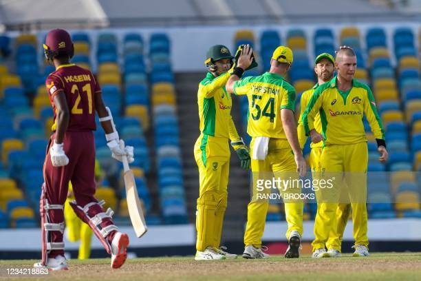 Adam Zampa , Matthew Wade and Alex Carey of Australia celebrate the dismissal of Akeal Hosein of West Indies during the 3rd and final ODI between...