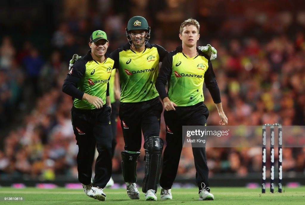 Adam Zampa of Australia (R) celebrates with David Warner (L) and Alex Carey (C) of Australia after taking the wicket of Tom Blundell of New Zealand during game one of the International Twenty20 series between Australia and New Zealand at Sydney Cricket Ground on February 3, 2018 in Sydney, Australia.