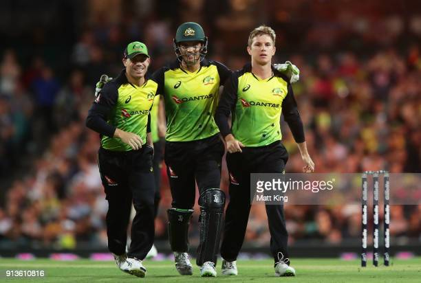 Adam Zampa of Australia celebrates with David Warner and Alex Carey of Australia after taking the wicket of Tom Blundell of New Zealand during game...
