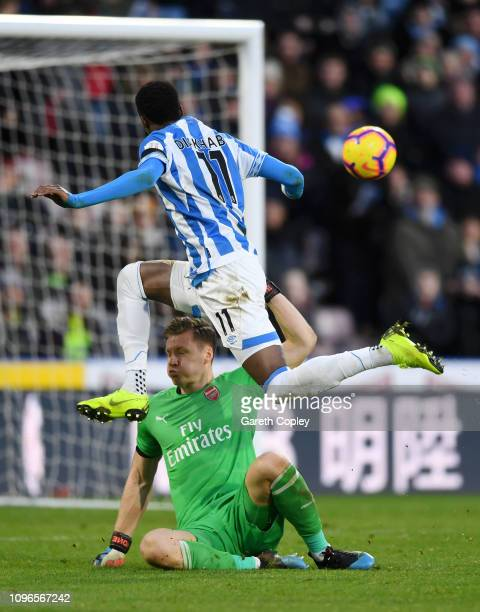 Adama Diakhaby of Huddersfield Town shoots under pressure from Bernd Leno of Arsenal which lead to an own goal by Sead Kolasinac of Arsenal for...