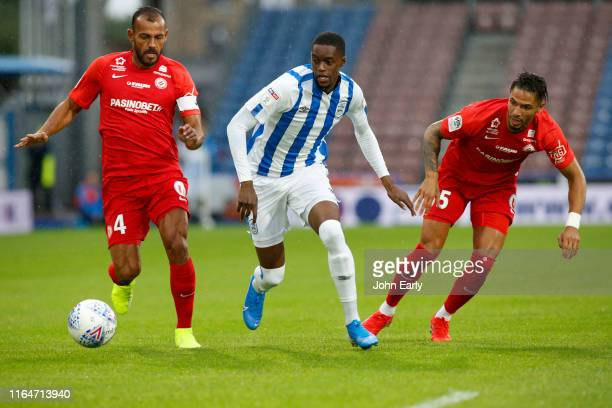 Adama Diakhaby of Huddersfield Town takes on Vitorino Hilton and Pedro Mendes of Montpellier at John Smith's Stadium on July 27 2019 in Huddersfield...