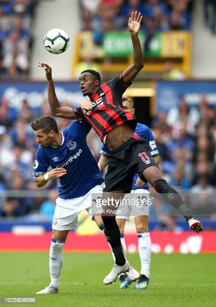 Adama Diakhaby of Huddersfield Town wins a header from Morgan Schneiderlin of Everton during the Premier League match between Everton FC and...