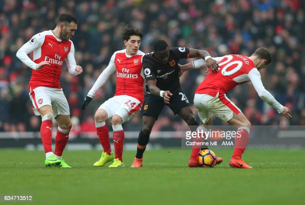 Adama Diomande of Hull City is hounded by Lucas Perez Hector Bellerin and Shkodran Mustafi of Arsenal during the Premier League match between Arsenal...