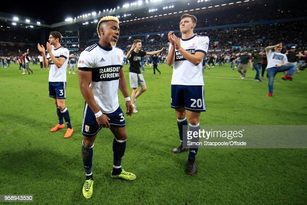 Adama Traore of Boro looks dejected alongside teammates George Friend of Boro and Dael Fry of Boro as home fans celebrate around them on the pitch at...