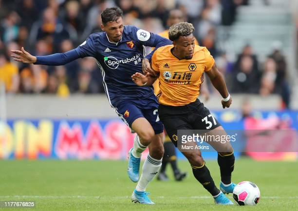 Adama Traore of Wolverhampton Wanderers battles for possession with Jose Holebas of Watford during the Premier League match between Wolverhampton...