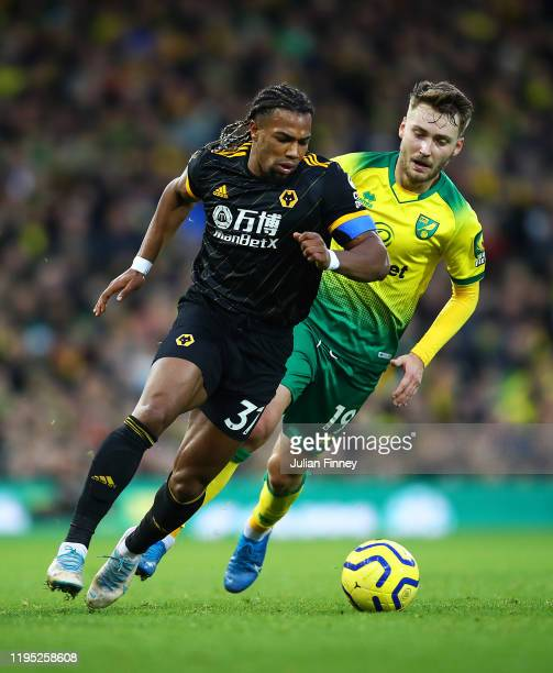 Adama Traore of Wolverhampton Wanderers battles for possession with Tom Trybull of Norwich City during the Premier League match between Norwich City...