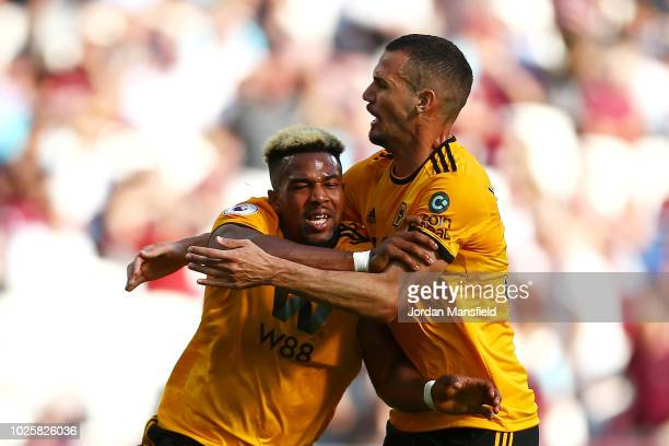 Adama Traore of Wolverhampton Wanderers celebrates with teammate Leo Bonatini after scoring his team's first goal during the Premier League match...