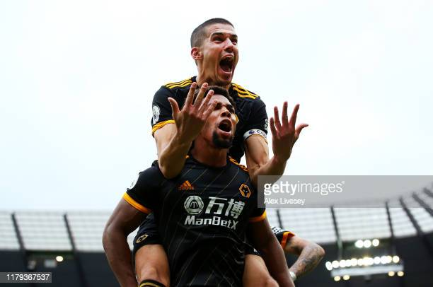 Adama Traore of Wolverhampton Wanderers celebrates with teammate Conor Coady after scoring his team's first goal jumps on top during the Premier...