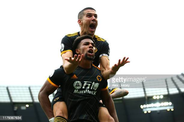 Adama Traore of Wolverhampton Wanderers celebrates with teammate Conor Coady after scoring his team's first goal during the Premier League match...