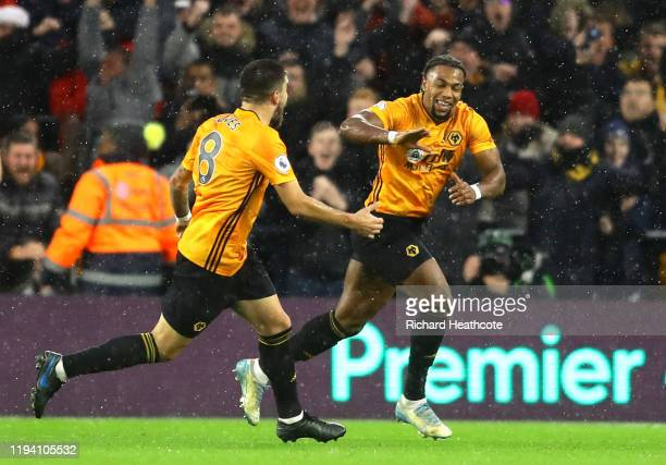 Adama Traore of Wolverhampton Wanderers celebrates with teammate Ruben Neves after scoring his team's first goal during the Premier League match...