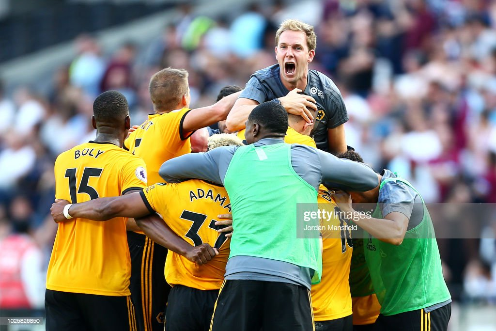 Adama Traore of Wolverhampton Wanderers celebrates with teammates and staff after scoring his team's first goal during the Premier League match between West Ham United and Wolverhampton Wanderers at London Stadium on September 1, 2018 in London, United Kingdom.