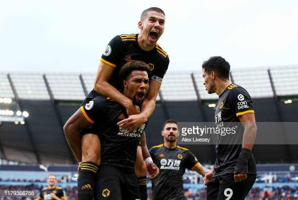 Adama Traore of Wolverhampton Wanderers celebrates with teammates after scoring his team's first goal as Conor Coady jumps on top during the Premier...