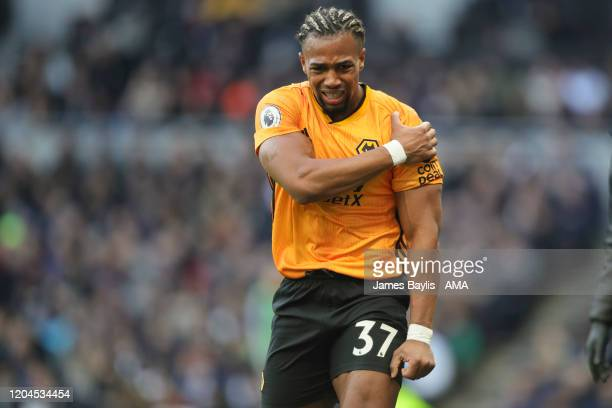 Adama Traore of Wolverhampton Wanderers clutches his injured shoulder during the Premier League match between Tottenham Hotspur and Wolverhampton...