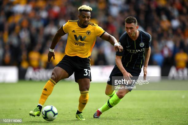 Adama Traore of Wolverhampton Wanderers controls the ball as Aymeric Laporte of Manchester City looks on during the Premier League match between...