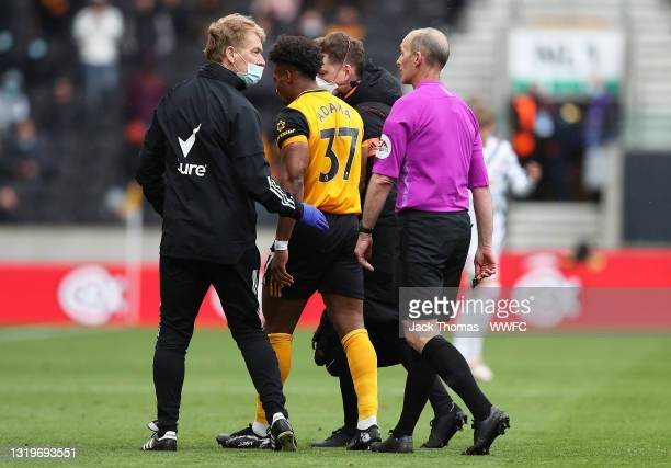 Adama Traore of Wolverhampton Wanderers is assisted off the pitch by Matt Perry, Club Doctor of Wolverhampton Wanderers and Ollie Leaper, Physio of...