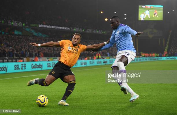 Adama Traore of Wolverhampton Wanderers is challenged by Benjamin Mendy of Manchester City during the Premier League match between Wolverhampton...