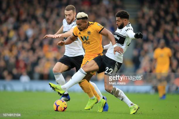 Adama Traore of Wolverhampton Wanderers is challenged by Calum Chambers of Fulham and Cyrus Christie of Fulham during the Premier League match...
