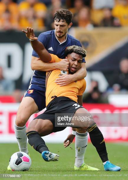 Adama Traore of Wolverhampton Wanderers is challenged by Craig Cathcart of Watford during the Premier League match between Wolverhampton Wanderers...
