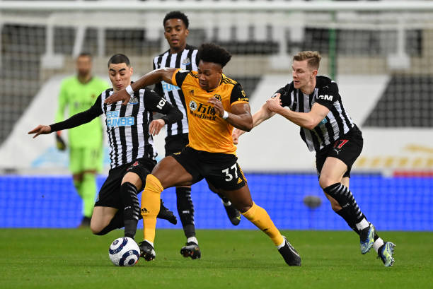 Adama Traore of Wolverhampton Wanderers is challenged by Emil Krafth and Miguel Almiron of Newcastle United during the Premier League match between...