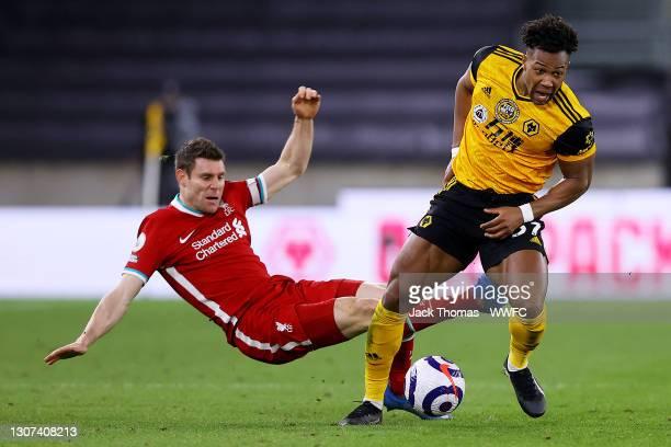 Adama Traore of Wolverhampton Wanderers is challenged by James Milner of Liverpool during the Premier League match between Wolverhampton Wanderers...