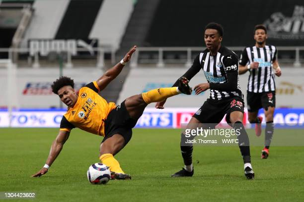 Adama Traore of Wolverhampton Wanderers is challenged by Joe Willock of Newcastle United during the Premier League match between Newcastle United and...