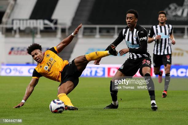 Adama Traore of Wolverhampton Wanderers is challenged by Joseph Willock of Newcastle United during the Premier League match between Newcastle United...