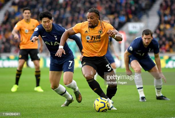 Adama Traore of Wolverhampton Wanderers is put under pressure by HeungMin Son of Tottenham Hotspur during the Premier League match between...