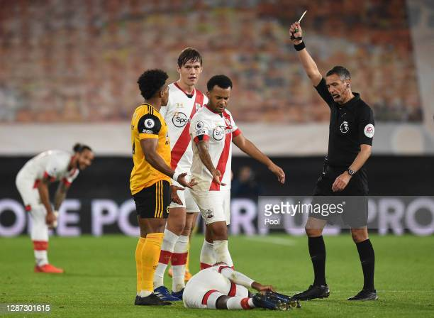Adama Traore of Wolverhampton Wanderers is shown a yellow card by referee Andre Marriner for a foul on Moussa Djenepo of Southampton as Jannik...