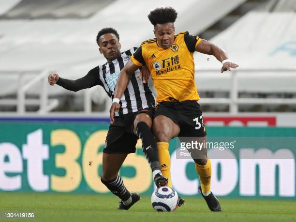 Adama Traore of Wolverhampton Wanderers is tackled by Joe Willock of Newcastle United during the Premier League match between Newcastle United and...