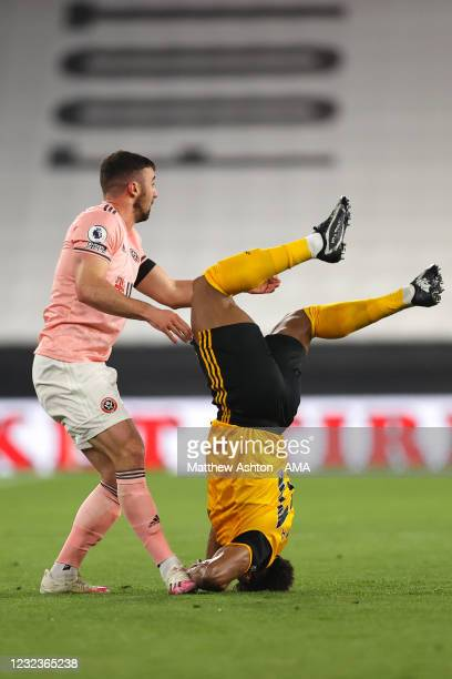 Adama Traore of Wolverhampton Wanderers lands awkwardly under a challenge from Enda Stevens of Sheffield United during the Premier League match...
