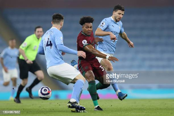 Adama Traore of Wolverhampton Wanderers passes the ball whilst under pressure from Rodri and Ruben Dias of Manchester City during the Premier League...
