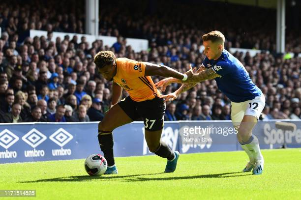 Adama Traore of Wolverhampton Wanderers run with the ball while pressured by Lucas Digne of Everton during the Premier League match between Everton...