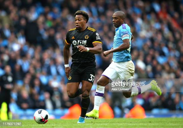 Adama Traore of Wolverhampton Wanderers runs past Fernandinho of Manchester City before scoring his teams second goal during the Premier League match...