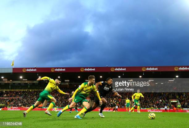 Adama Traore of Wolverhampton Wanderers runs past Tom Trybull of Norwich City during the Premier League match between Norwich City and Wolverhampton...
