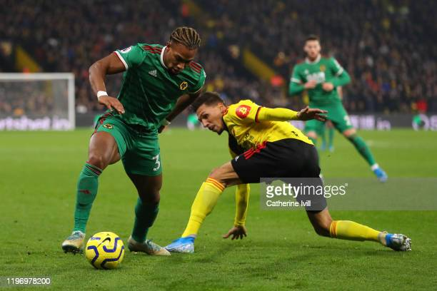 Adama Traore of Wolverhampton Wanderers runs with the ball past Jose Holebas of Watford during the Premier League match between Watford FC and...