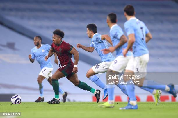 Adama Traore of Wolverhampton Wanderers runs with the ball past Rodri of Manchester City during the Premier League match between Manchester City and...