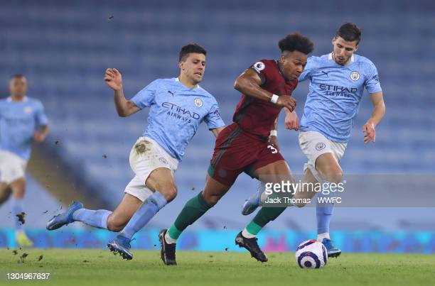 Adama Traore of Wolverhampton Wanderers runs with the ball past Rodri and Ruben Dias of Manchester City during the Premier League match between...