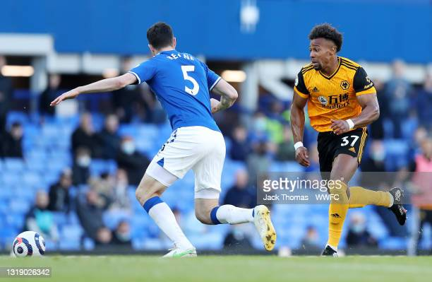 Adama Traore of Wolverhampton Wanderers runs with the ball under pressure from Michael Keane of Everton during the Premier League match between...