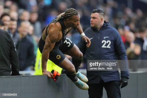 Adama Traore of Wolverhampton Wanderers vaults over the advertising boards after giving his shirt to a young Wolves fan during the Premier League...