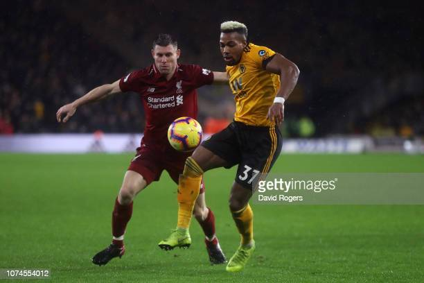 Adama Traore of Wolves holds off pressure from James Milner of Liverpool during the Premier League match between Wolverhampton Wanderers and...
