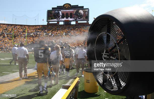 E Adams Aqua Breeze misting fan is used on the sidelines to cool players during the matchup between the Iowa Hawkeyes and the Northern Illinois...
