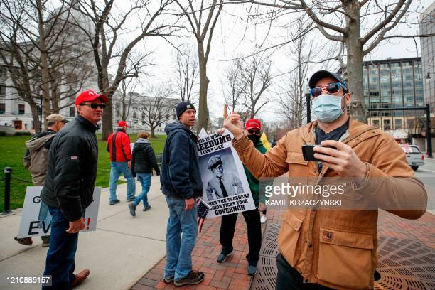 JJ Adams argues with protesters against the coronavirus shutdown in front of State Capitol in Madison Wisconsin on April 24 2020 The coronavirus...