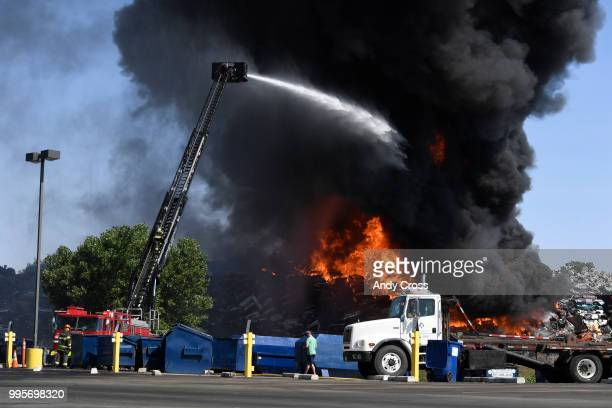 Adams County firefighters try to get control of a fire in a large pile of crushed vehicles near 5600 York St July 10 2018