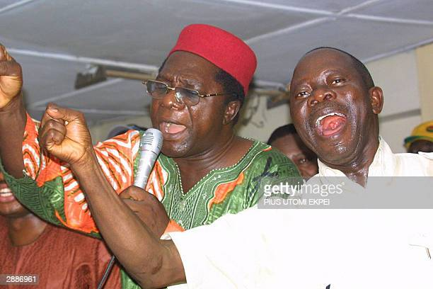Adams Oshiomhole leader of the Nigeria Labour Congress and his deputy Joseph Akinlaja sing the union's slogan at its Lagos secretariat 21 January...