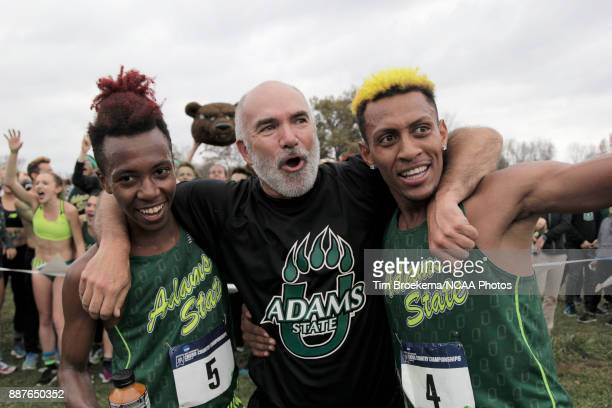 Adams State University head coach Damon Martin center celebrates with Sydney Gidabuday left and Elias Geydon during the Division II Men's Cross...