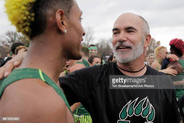 Adams State University head coach Damon Martin center celebrates with Elias Geydon left during the Division II Men's Cross Country Championship held...