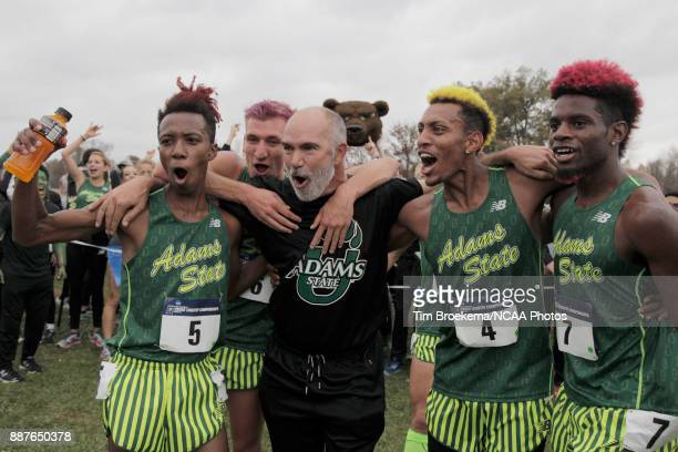 Adams State University runners celebrate with head coach Damon Martin center during the Division II Men's Cross Country Championship held at the...