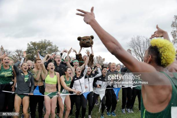Adams State University supporters cheer with Elias Gedyon during the Division II Men's Cross Country Championship held at the Angel Mounds on...