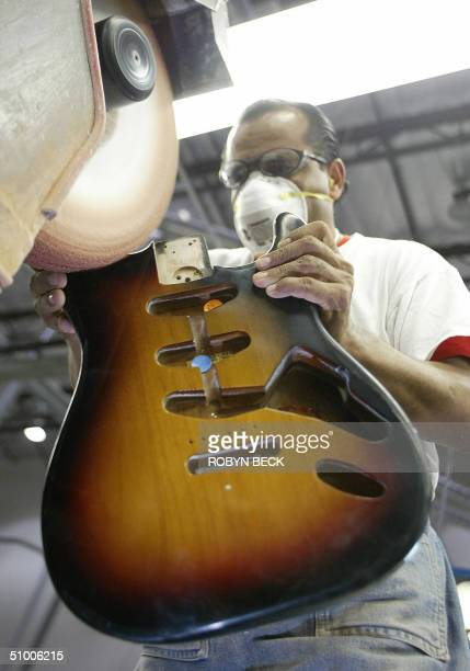Adan Alcantar polishes the edges of a Stratocaster body at the Fender manufacturing facility in Corona California 28 June 2004 The sainted...